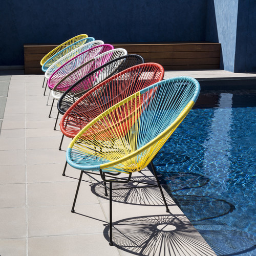 colorful acapulco chair next to the swimming pool