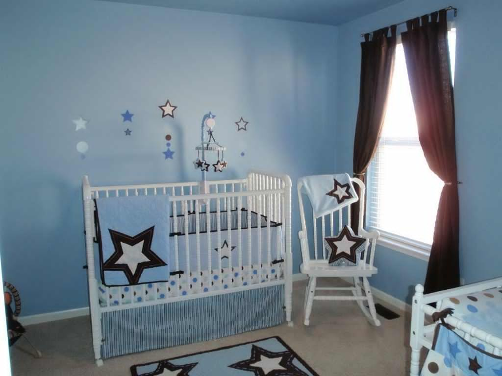 baby crib in a blue room for baby boy with rocking chair besides