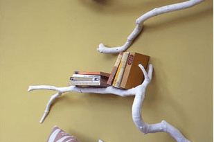tree branch bookshelf on a yellow wall