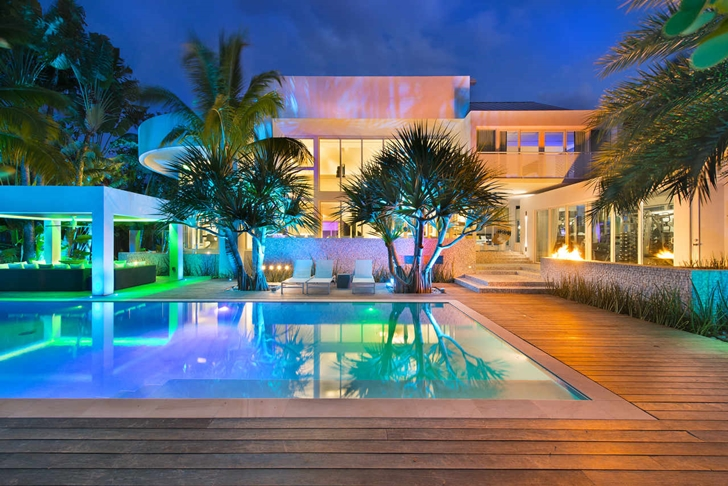 florida mansion swimming pool at night with full lighting