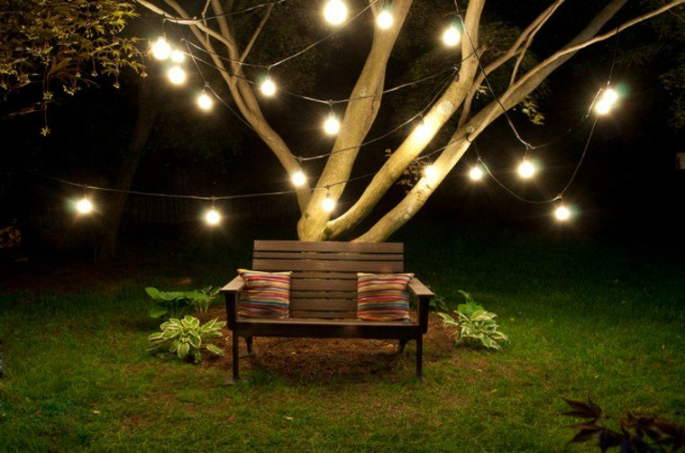 romantic outdoor lighting on a tree and a couple seat