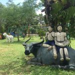two khmer children on a buffalo statue in an organic farm