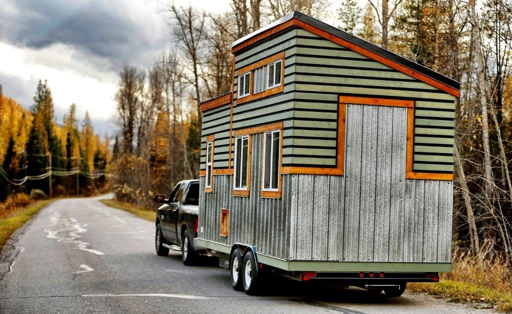 a wooden home on wheel driven by a pick up truck