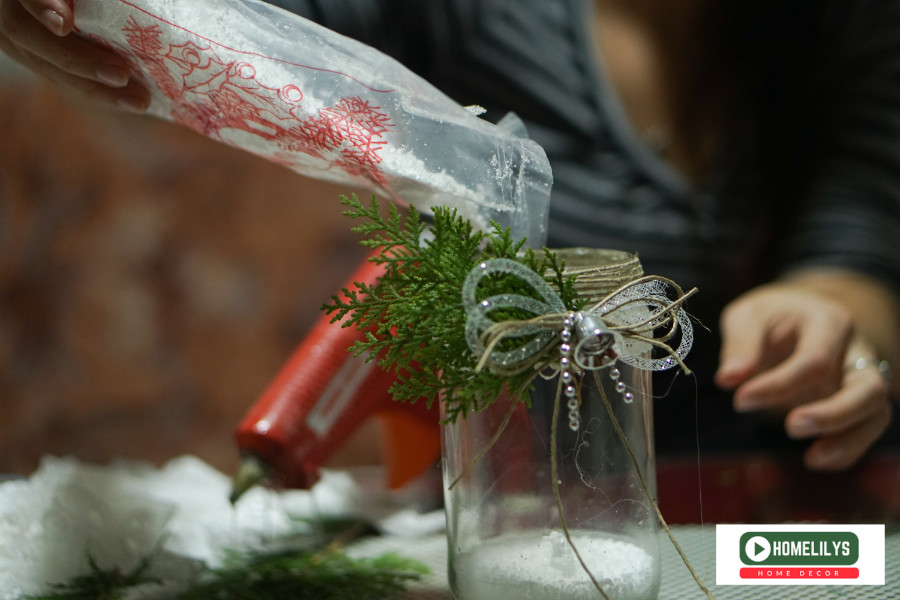 adding fake snow flakes into the old jam jar